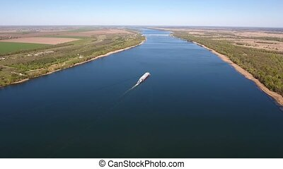 Aerial shot of a slowly moving ship down the dnipro river in spring