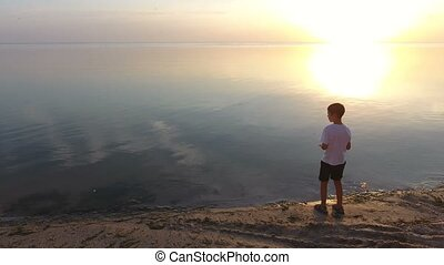 Aerial shot of a small boy standing on a seashore and watching the Black Sea