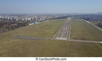 Aerial shot of a small propeller airplane flying near city airport runway on a sunny day. 4K video