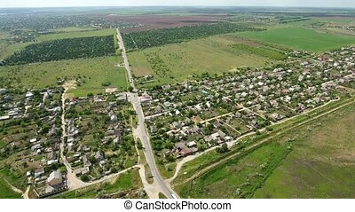 Aerial shot of a small village  in Ukraine located among green fields in spring