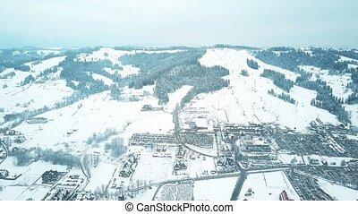 Aerial shot of a snow covered mountain skiing slopes. Bialka Tatrzanska ski resort in the Tatra mountains, southern Poland