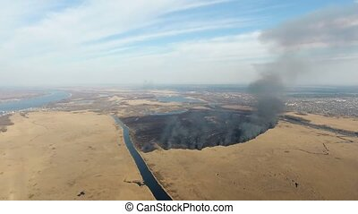 Aerial shot of a splendid sky and burning black reed area at...