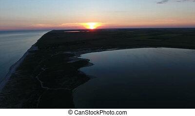 Aerial shot of a  splendid sunset over a triangular island in the Black Sea