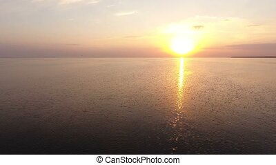 Aerial shot of a splendid sunset over sparkling sea waters...