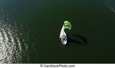 Aerial shot of a splendid yacht with multicolored sail...