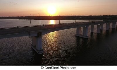 Aerial shot of a straight bridge at violet sunset from a...