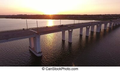 Aerial shot of a straight bridge over the Dnipro at golden...