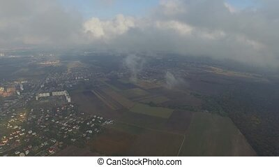 Aerial shot of a suburb, field, the forest in the clouds.