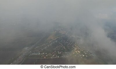 Aerial shot of a suburb, the main road, the forest in the clouds. 360 degree swivel.