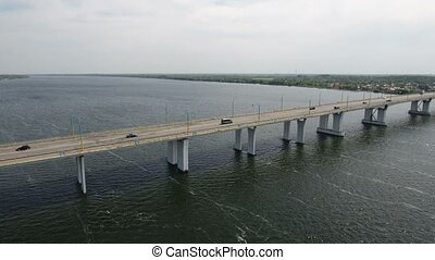 Aerial shot of a too long asphalt bridge over the Dnipro in summer