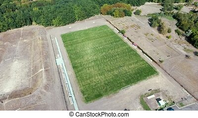 Aerial shot of a trim football field with mowed grass in...