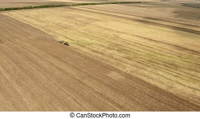 Aerial shot of a Ukrainian field and a farm tractor pulling a harrow in summer