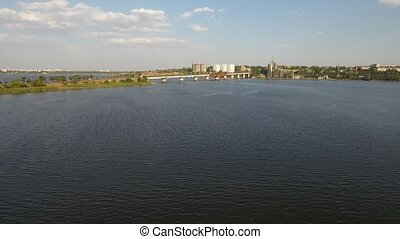 A beautiful bird`s eye view of a long modern bridge over the Southern Bug. A part of it goes along a narrow stripe of land. The summer skyscape is gorgeous. The riverbank is dark green