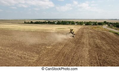 Aerial shot of a vast field and a big tractor pulling a harrow in summer