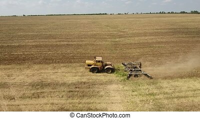 Aerial shot of a vast field and a big tractor pulling a...