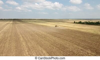 Aerial shot of a vast field and a farm tractor pulling a...