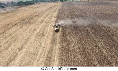 Aerial shot of a wheat field and a farm tractor pulling a harrow in summer