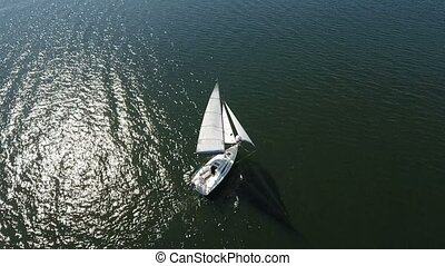 Aerial shot of a white one mast yacht sailing in the dark blue river waters