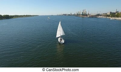 Aerial shot of a white one mast yacht sailing in the Dnipro on a sunny day