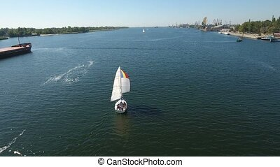 Aerial shot of a white one mast yacht sailing in the sparkling blue river waters