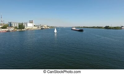 Aerial shot of a white yacht and a barge competing in the Dnipro on a sunny day