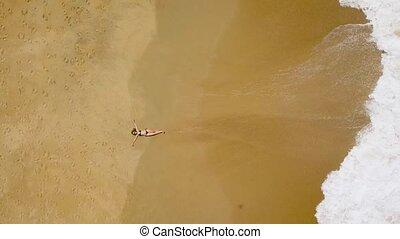 aerial shot of a woman in a bikini lying on a sandy beach and waves wash her feet