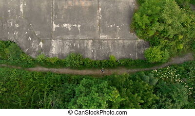 Aerial shot of a young man running at the territory of an...