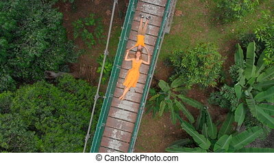 Aerial shot of a young woman and her little son laying on a suspension bridge over the jungles. Travel to South East Asia concept
