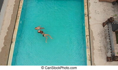 Aerial shot of a young woman and her little son tourists having a good time in a swimming pool in a tropical surrounding. Tropical life concept.