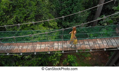 Aerial shot of a young woman and her little son walking on a suspention bridge over the jungles. Vacation in tropics concept