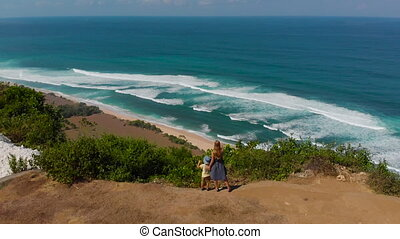 Aerial shot of a young woman and her son visiting a remote beach - nyang nyang- on the Bali island. Standing on a rock looking at an open ocean in front of them