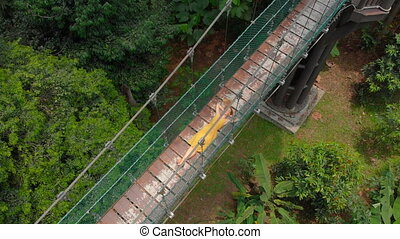 Aerial shot of a young woman lays on a suspension bridge over the jungles. Travel to South East Asia concept