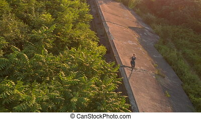 Aerial shot of a young woman running on top of an old 1st...