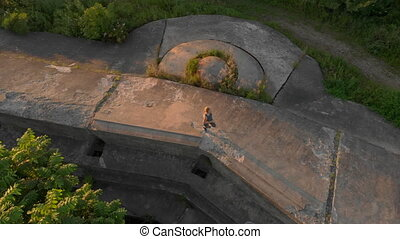 Aerial shot of a young woman running on top of an old 1st world war fortress during sunset, sunrise