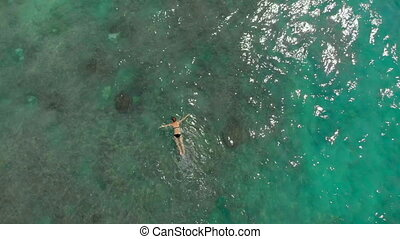 Aerial shot of a young woman snorkeling in an open sea watching corals and exotic fishes.