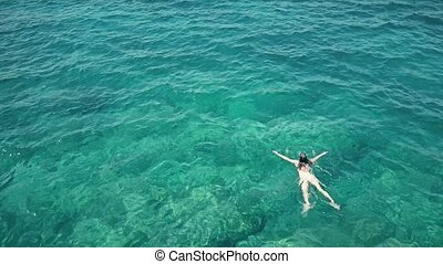 Aerial shot of a young woman swimming in the sea - Aerial...