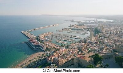 Aerial shot of Alicante cityscape and seaport behind Santa Barbara castle
