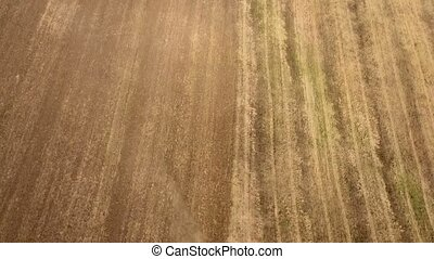 Aerial shot of an a country field and a big tractor pulling a harrow in summer