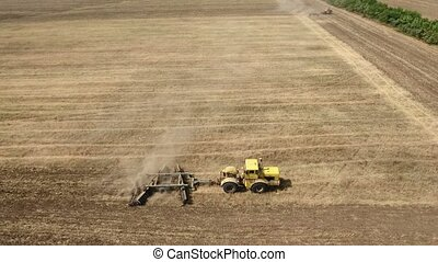 Aerial shot of an agricultural field and a yellow tractor pulling a harrow