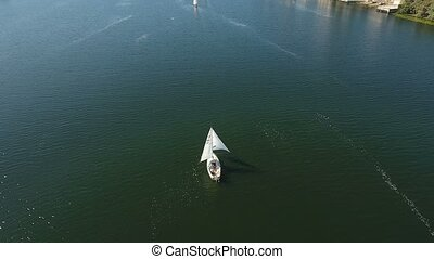 Aerial shot of an arty white yacht sailing in the Dnipro dark blue river waters