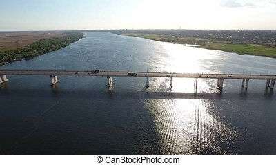 Aerial shot of an automobile bridge over the Dnipro river in a sunny day