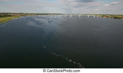 Aerial shot of an automobile bridge over the Dnipro river in the evening