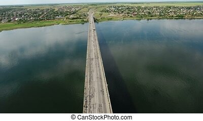 Aerial shot of an automobile bridge with a drone flying over it in summer