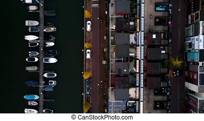 aerial shot of an urban area houses next to the water with small docks boats residential area