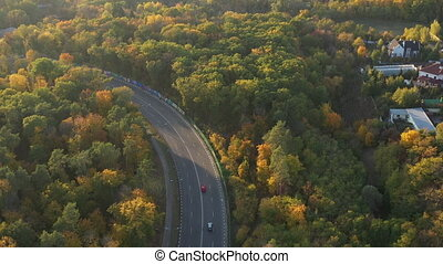 Aerial shot of beautiful colorful forest in the fall. Top view of the corner of a country road. The beautiful nature of autumn inspires a walk in the forest. Roads and rich houses in behind the trees.