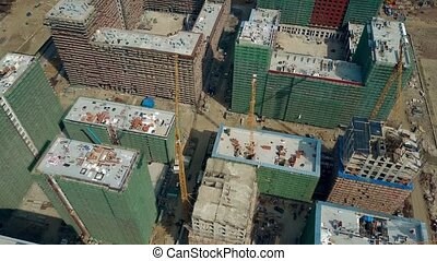 Aerial shot of big construction site. Rooftops of unfinished modern apartment buildings. 4K video