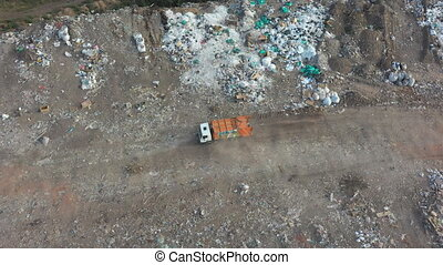 Aerial shot of big rubbish pile lying among field in countryside. Flying over garbage truck dumping trash at open places outdoor. Global environmental pollution problem. Top view Slow motion.