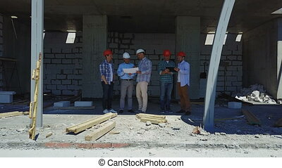Aerial Shot Of Builders Team On Construction Site Discussing Plan Of Project With Architect And Contractor Using Blueprint