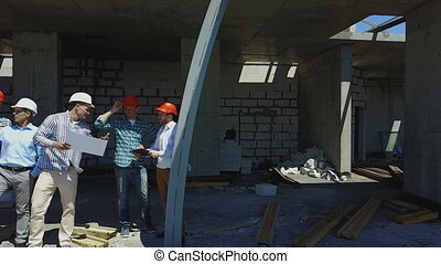 Aerial Shot Of Builders Team On Construction Site Discussing...