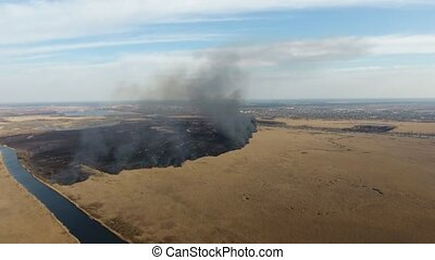Aerial shot of burning cane and reed marshes at the Dnipro river inflows in spring
